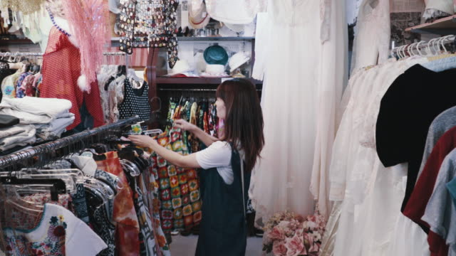 Young female customer shopping for vintage clothing in a thrift store