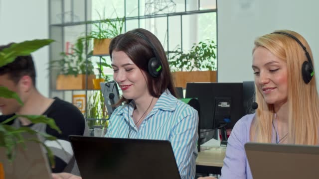 Young female customer support operator wearing headset, answering calls