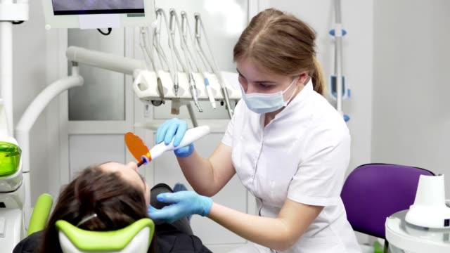 Jeune dentiste femme au masque et des gants à l'aide de matériel de lumière UV dentaire pour la trempe de polymère - Vidéo