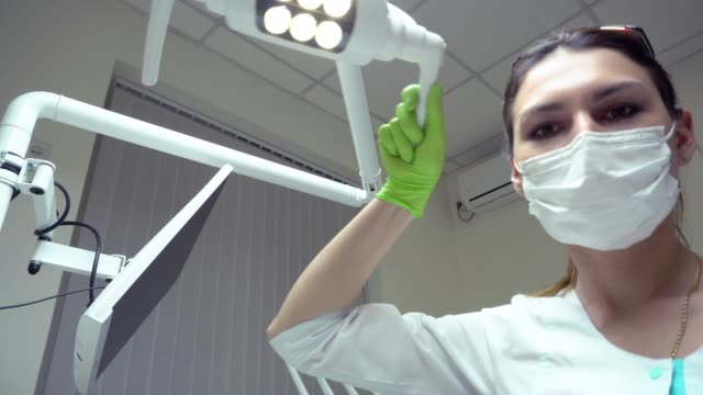 Young Female Dentist in mask and protective gloves turns the light of dental lamp on, standing upon a patient. Looking at camera, Shot in 4k video