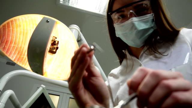 Dentista mujer joven en la máscara se acerca con herramientas, sosteniendo un espejo de boca y el gancho del dentista, Dental lámpara luces en boca de un paciente, de pie sobre un paciente, mirando a cámara, cara del dentista - vídeo
