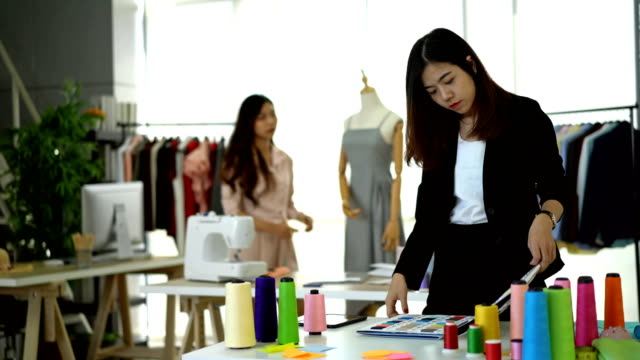 Young Female Designer Asking Customer Requirement With Her Colleague In The Background 4K Young Female Designer Asking Customer Requirement With Her Colleague In The Background fabric swatch stock videos & royalty-free footage