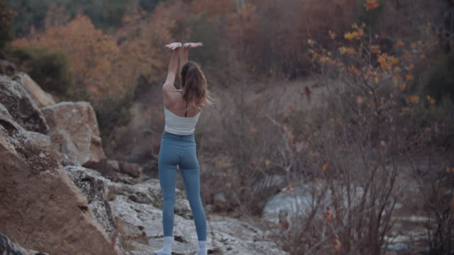 genç kadın doğada germe egzersizleri yapmak - 10 saniyeden fazla stok videoları ve detay görüntü çekimi