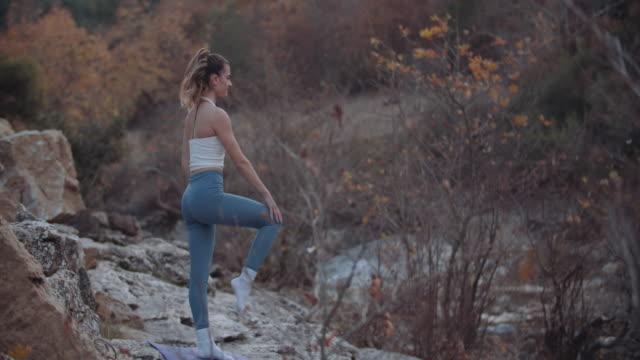 vídeos y material grabado en eventos de stock de mujer joven hace ejercicios de estiramiento en la naturaleza - diez segundos o más