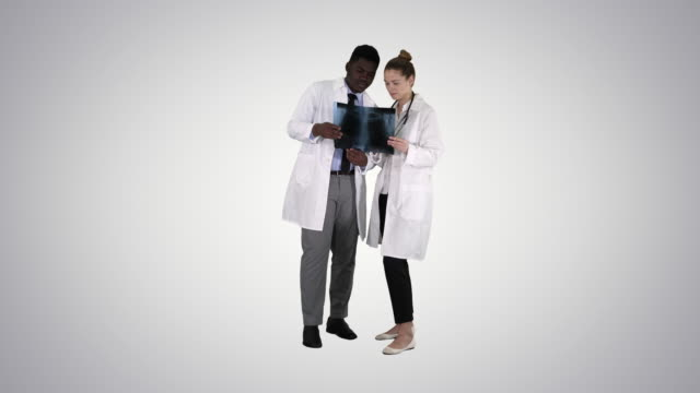 vídeos de stock e filmes b-roll de young female doctor and afro american doctor looking at the x-ray picture of lungs on gradient background - afro americano