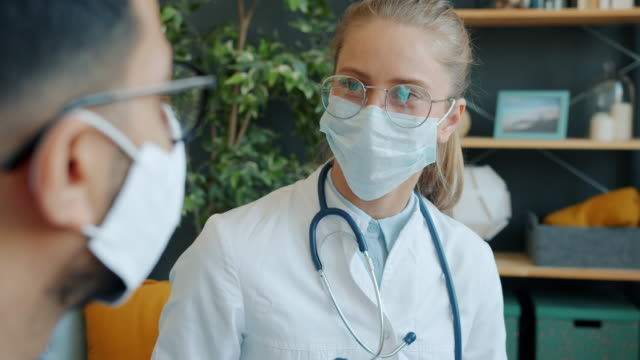 Young female doctor in face mask talking to male patient at home while man couching video