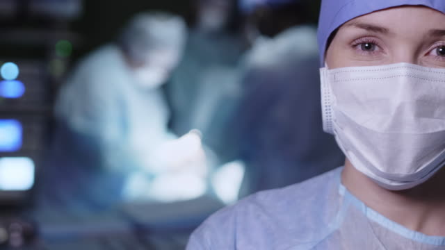 young female doctor standing in operation room - face mask stock videos & royalty-free footage