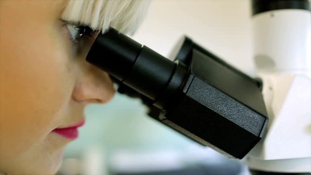 Young female Doctor with a microscopic examination video