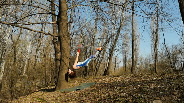 Young female doing the aerogravity exercises on ropes outdoors Young woman practicing aerogravity in the park. The woman makes physical exercises on the ropes on tree. Flexible female hanging on the ropes and stretching her body and muscles. She's moving slowly and accuracy. arthropod stock videos & royalty-free footage