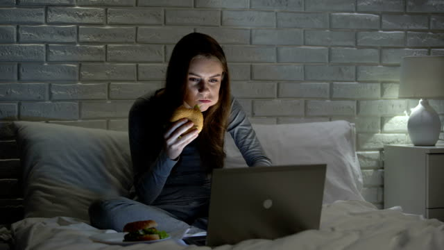 young female eating hamburger while surfing web at night on bed, junk food - junk food stock videos and b-roll footage