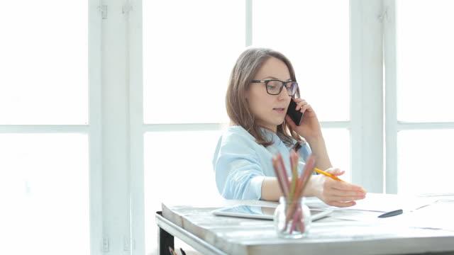 stockvideo's en b-roll-footage met jonge vrouwelijke ondernemer praten aan de telefoon in haar kantoor. - business woman phone