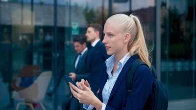 slo mo ts young unternehmerin zu fuß entlang eines geschäftsgebäudes beim scrollen ihres smartphones - weibliche angestellte stock-videos und b-roll-filmmaterial