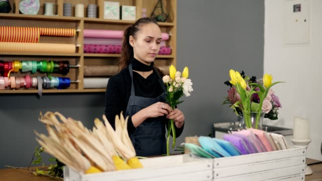 Young female florist arranging modern bouquet at flowers shop standing by the table. She combines creamy roses and yellow tulips video