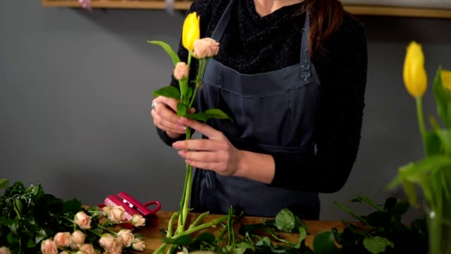 Young female florist arranging modern bouquet at flowers shop. She combines creamy roses and yellow tulips. Slowmotion shot video