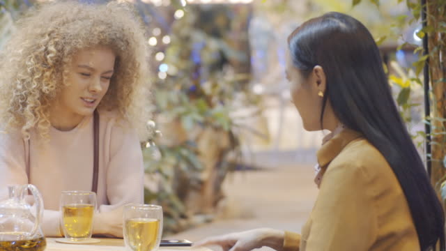 young female friends chatting over tea in cafe - femminilità video stock e b–roll