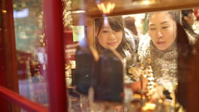 junge freundinnen einkaufen am weihnachtsmarkt - weihnachtsmarkt stock-videos und b-roll-filmmaterial