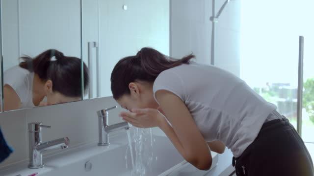若い女性は、浴室の準備します。 ビデオ