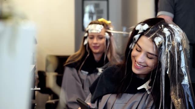 若い女性の脱毛サロン顧客は新しい髪の色を設定するの待ちながらスマート フォンを使用してください。 - 美容室のビデオ点の映像素材/bロール