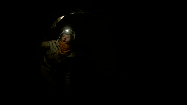 Young female hiker with flashlight explored the dark cave