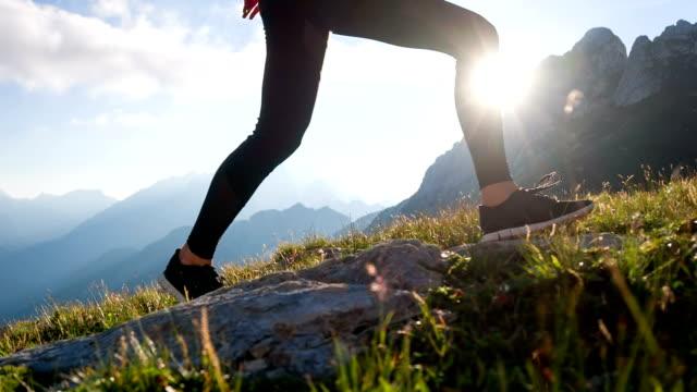 young female hiking up a mountain - posizione corretta video stock e b–roll