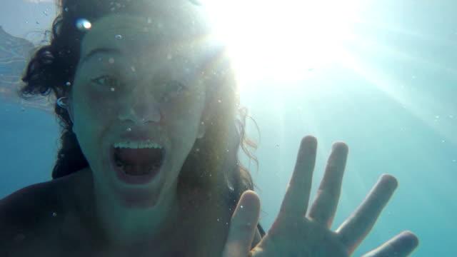 ung kvinna i en pool som har roligt under vattnet och blåsa kyssar till kameran - blåsa en kyss bildbanksvideor och videomaterial från bakom kulisserna