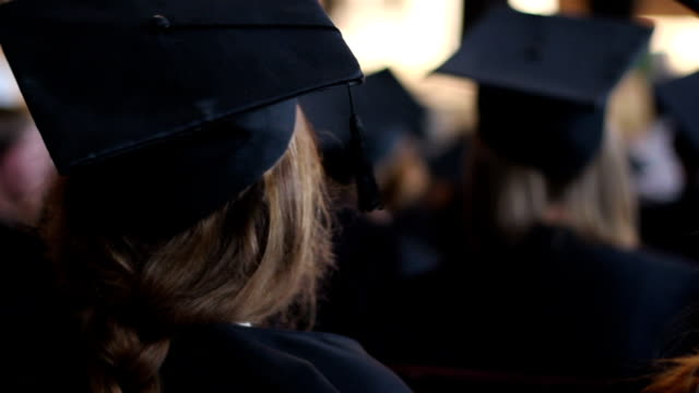 Young female in academic dress at diploma award ceremony, listening video