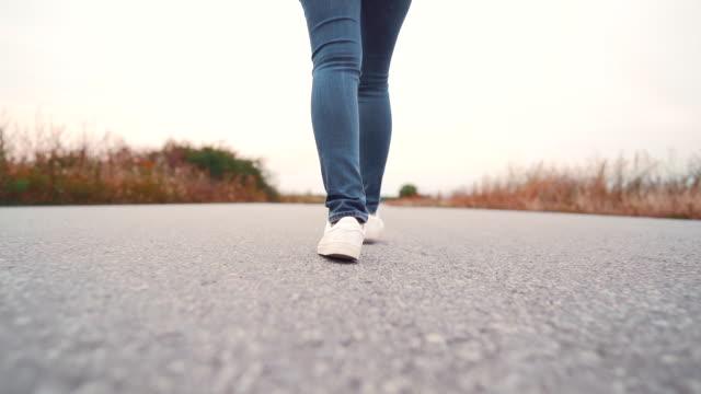 vídeos y material grabado en eventos de stock de joven mujer en zapatos de mezclilla y de moda caminando por camino asfaltado liso. concepto de zapatillas modernas, viajes, senderismo. disparo trasero. - andar