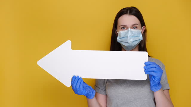 Young female in medical face mask and gloves hold white paper arrow, points sideways, dressed in grey t-shirt, isolated on yellow background with copy space for advertisement. Coronavirus concept