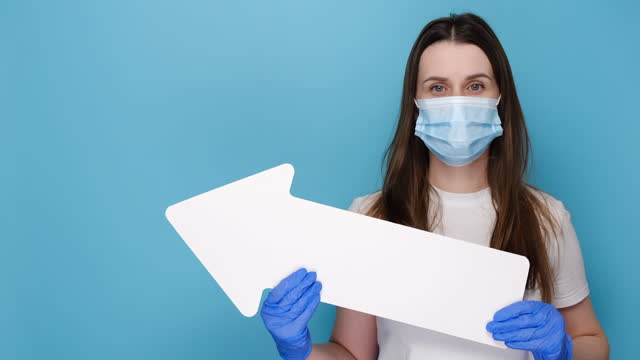 Young female in medical protective face mask and latex gloves holding paper arrow, wears white t-shirt, isolated on blue background with copy space for advertisement. Pandemic coronavirus concept