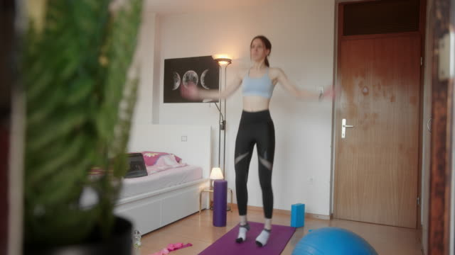 Young female in quarantine doing home exercises next to tablet with video workout