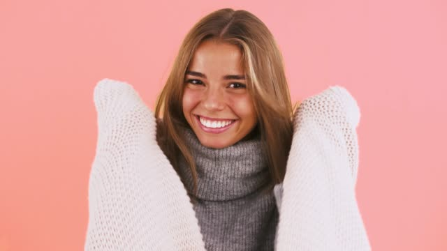 Young female in sweater is feeling cold, wrapping herself up with a blanket and laughing while posing on pink background