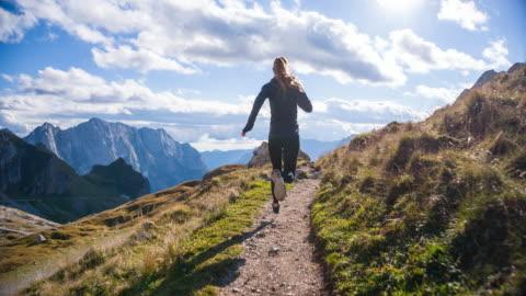vídeos de stock e filmes b-roll de young female in the mountains running away from camera - correr