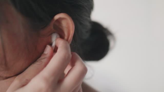 young female inserting earphones in bedroom. - cuffia attrezzatura per l'informazione video stock e b–roll