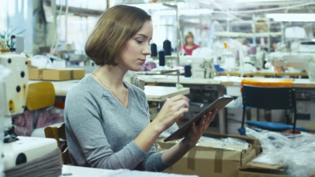 Young female is sitting at a table in a clothing factory and sketching on a tablet with a stylus. video