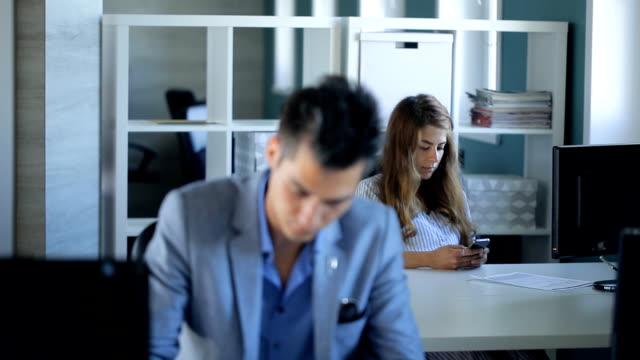Mujer joven está esperando trabajo final sentado en oficina - vídeo