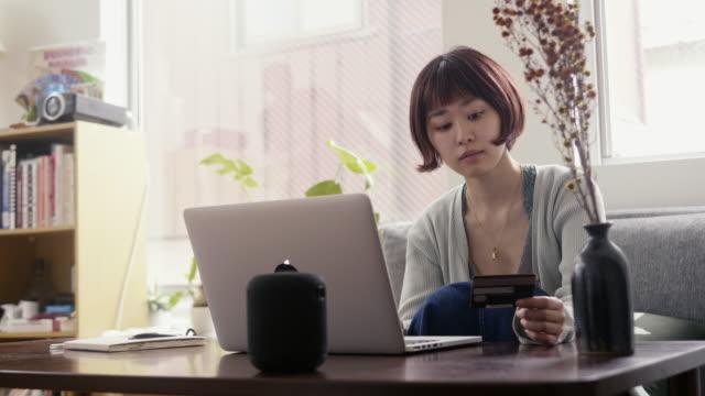 vidéos et rushes de jeune adulte japonais féminin faisant des emplettes en ligne avec la carte de crédit - seulement des japonais