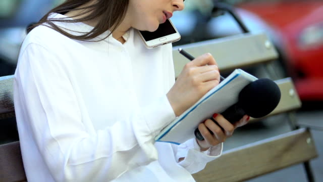 Young female journalist writing notebook talking on phone holding microphone