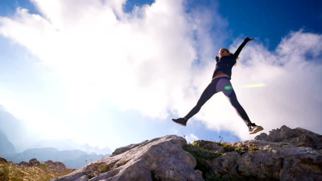 Young female jumps into the sky in the mountains video