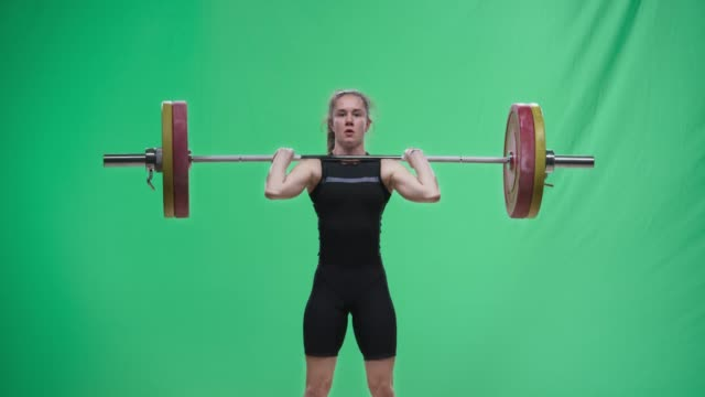 Young female lifter performing the clean and jerk lift