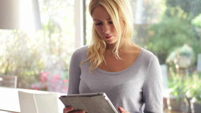 Young female looking at ipad and drinking tea in kitchen video