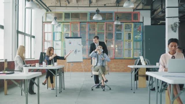 若い女性マネージャーがオフィスの周りの椅子に乗って、お金を投げ出しています。彼女は同僚に助けられている。クリエイティブなオフィスインテリア。コワーキングチーム。オフィスワ� ビデオ