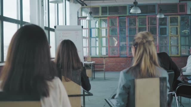 若い女性マネージャーがフリップチャートの近くに立ち、同僚にプレゼンテーションを行います。クリエイティブなオフィスインテリア。コワーキング。オフィスライフ。労働者 ビデオ
