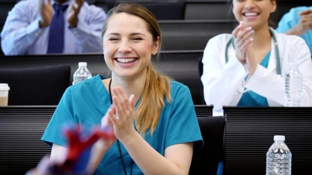若い女性の医療研修生が講義の後教授を称賛します。 ビデオ