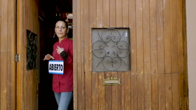 Young female Mexican chef holding an open sign in Spanish