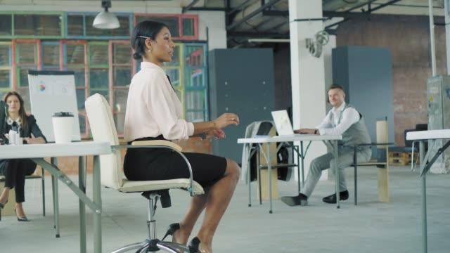 若い女性の男女混合レースマネージャーは、オフィスの椅子に乗って、ハイヒールの靴で足を押して楽しんでいます。フレンドリーで楽しいビジネスチーム。モダンなトレンディなインテリ� ビデオ