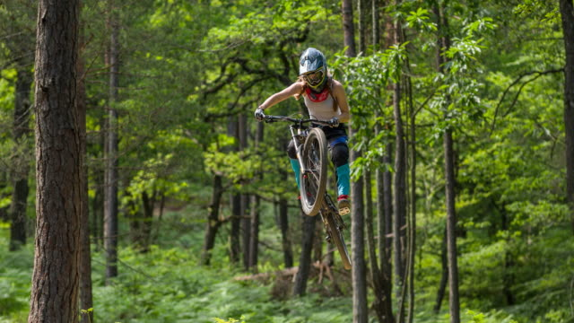 Young female mountain biker jumping towards the camera video