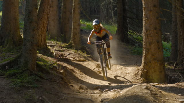 Young female mountain biker riding downhill a rocky dirt track video