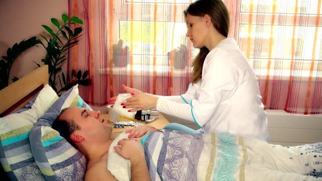 young female nurse taking care of her sick patient man in bed video