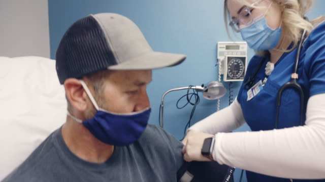 a young female nurse wearing a surgical face mask walks into an examination room of a medical clinic and places a blood pressure cuff on the arm of a masked white male in his forties - covid ospedale video stock e b–roll