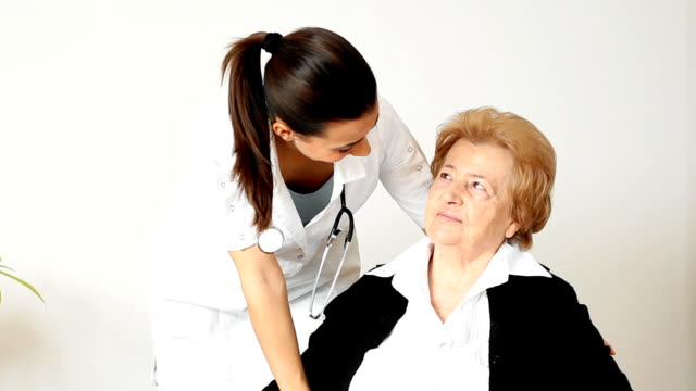 Young female nurse with her senior female patient. video